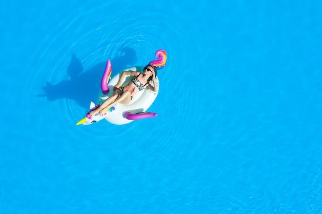 Widok z góry na basen z dziewczyną w stroju kąpielowym na nadmuchiwanym kółku. relaks i opalanie w lecie. Premium Zdjęcia