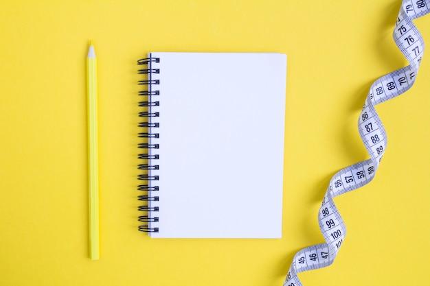 Widok Z Góry Na Biały Centymetr I Otwarty Notatnik Na żółtym Tle Premium Zdjęcia