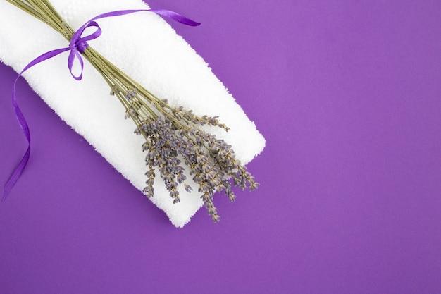 Widok Z Góry Na Biały Ręcznik I Bukiet Lawendy Suchej Na Fioletowym Tle Premium Zdjęcia