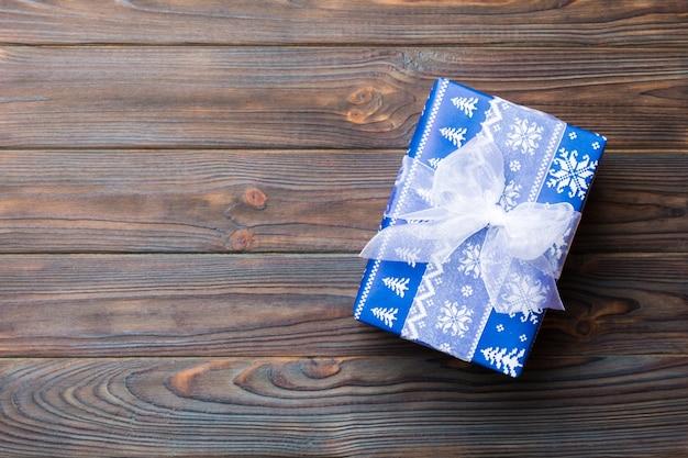 Widok z góry na boże narodzenie lub inny świąteczny ręcznie robiony prezentowy pakiet, płaskie ciemne drewniane miejsce. pudełko na prezent Premium Zdjęcia