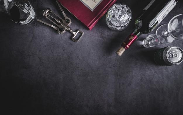 Widok z góry na butelkę wina, butelkę wódki, kostkę lodu, piwo i korkociąg Premium Zdjęcia
