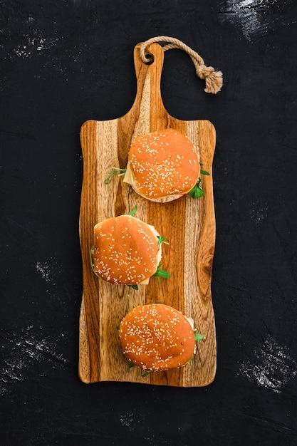 Widok Z Góry Na Domowy Burger Z Kotletem Z Kurczaka Na Długiej Desce Premium Zdjęcia