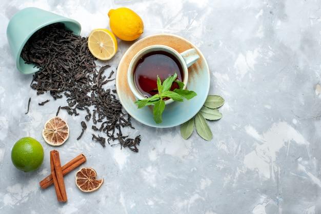 Widok Z Góry Na Filiżankę Herbaty Z Cytryną I Cynamonem Na Jasnym Stole, Suszone Owoce Cytrusowe Zbożowe Darmowe Zdjęcia