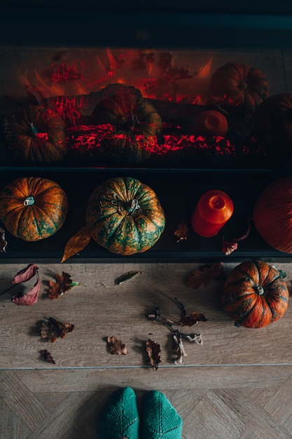 Widok Z Góry Na Kominek Ozdobiony Dyniami I Suchymi Jesiennymi Liśćmi Oraz Pomarańczową świecą. Przytulny Dom Koncepcja. Przygotowanie Do Halloween. Premium Zdjęcia