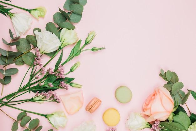 Widok z góry na makaroniki ze świeżą różą; limonium i eustoma kwiaty na różowym tle Darmowe Zdjęcia