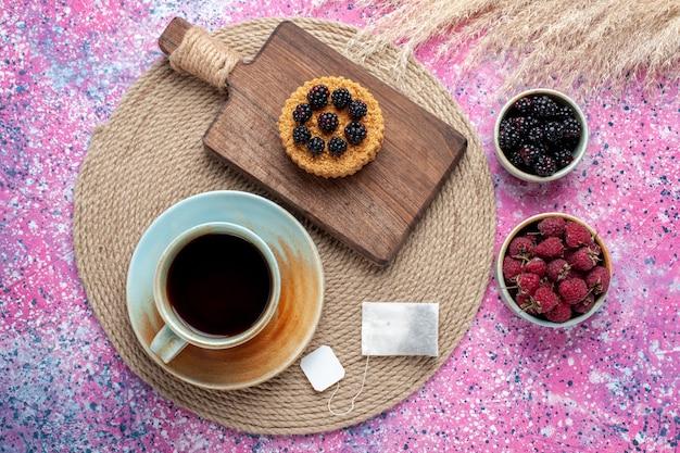 Widok Z Góry Na Małe Ciasto Z Różnymi Jagodami I Filiżanką Herbaty Na Różowej Powierzchni Darmowe Zdjęcia