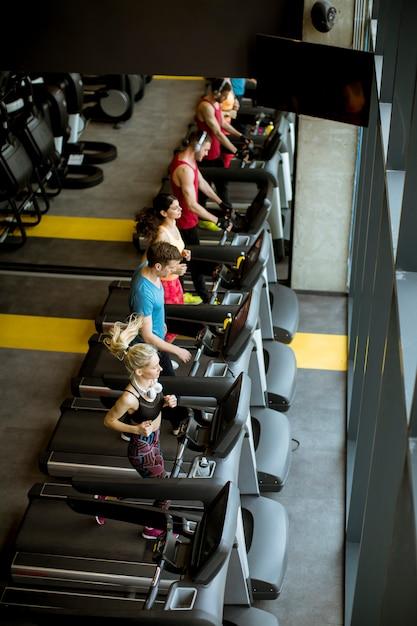 Widok z góry na młodych ludzi biegających na bieżniach w nowoczesnej siłowni Premium Zdjęcia