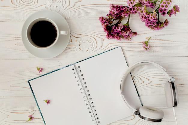 Widok z góry na pamiętnik lub notatnik, słuchawki, kawę i fioletowy kwiat na białym drewnianym stole. romantyczna płaska. Premium Zdjęcia