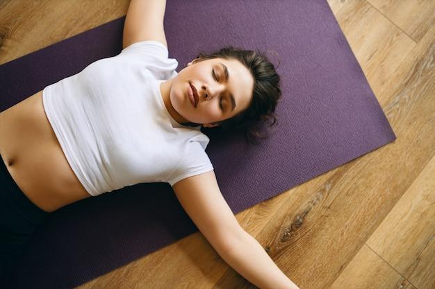 Widok Z Góry Na Piękną Młodą Kobietę W Białej Bluzce, Leżącą W Pozycji Shavasana Lub Trupa Podczas Zajęć Jogi, Odpoczywając Po Treningu, Medytując, Oddychając Głęboko. Koncepcja Relaksu I Odpoczynku Darmowe Zdjęcia