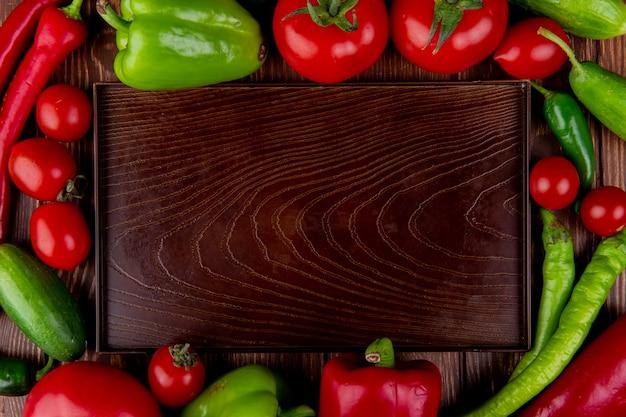 Widok Z Góry Na Pustą Drewnianą Tacę I świeże Warzywa Dojrzałe Pomidory Zielone I Czerwone Papryki Chili I Kolorowe Papryki Na Rustykalnym Darmowe Zdjęcia