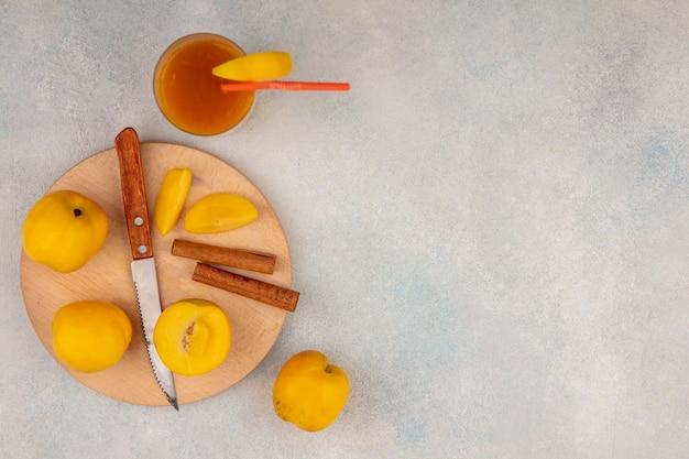 Widok Z Góry Na Pyszne żółte Brzoskwinie Na Drewnianej Desce Kuchennej Z Nożem Z Laskami Cynamonu Na Białym Tle Z Miejsca Na Kopię Darmowe Zdjęcia