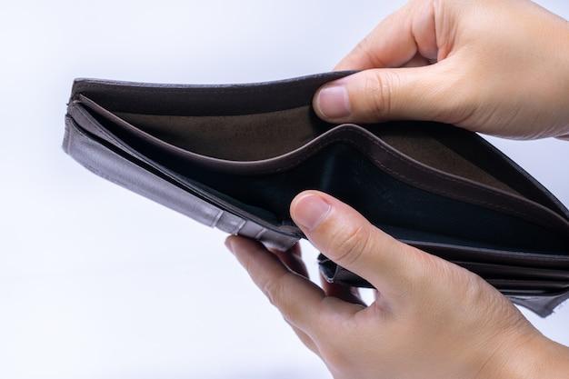 Widok z góry na ręce otwierające pusty portfel ze skóry Premium Zdjęcia
