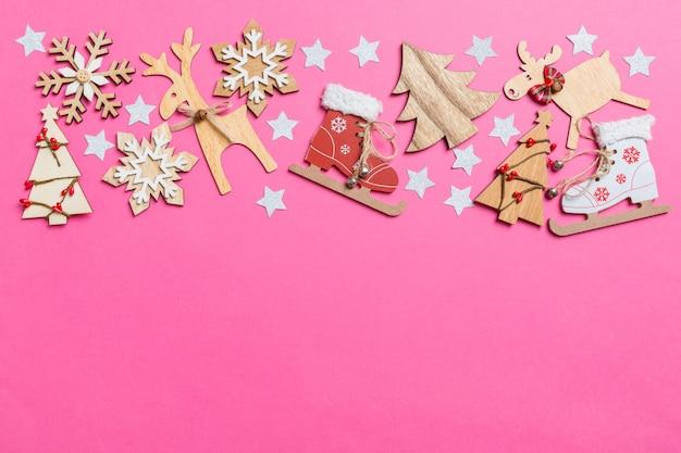Widok Z Góry Na Różowym Tle Ozdobione świątecznymi Zabawkami I Symbolami świąt Bożego Narodzenia Reniferów I Drzew Nowego Roku. Koncepcja Wakacje Z Miejsca Kopiowania Premium Zdjęcia