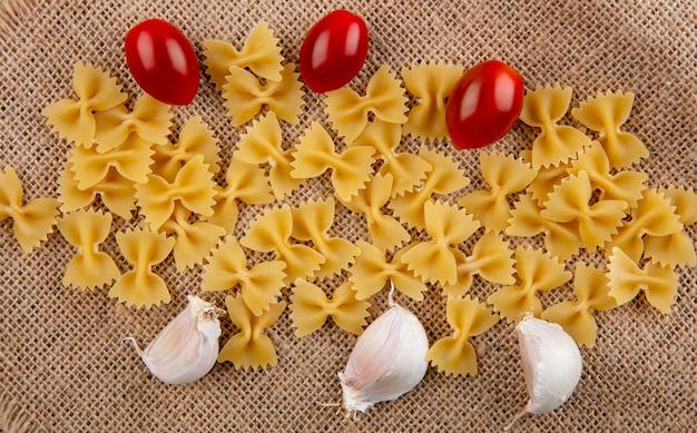 Widok Z Góry Na Surowe Spaghetti Z Pomidorkami Cherry I Czosnkiem Na Beżowej Serwetce Darmowe Zdjęcia