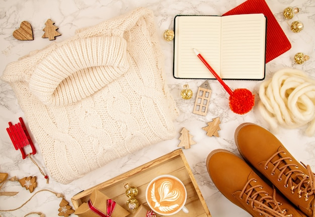 Widok Z Góry Na świąteczną Kompozycję Z Ciepłym Swetrem, Prezentami, świątecznymi Lampkami I Kawą Premium Zdjęcia