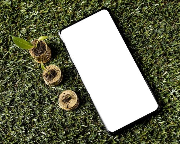 Widok Z Góry Na Trzy Stosy Monet Na Trawie Z Smartphone Darmowe Zdjęcia