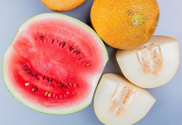 Widok Z Góry Na Wzór Ciętych I Całych Owoców Jak Arbuz I Melon Na Niebieskawo-szarym Tle Darmowe Zdjęcia