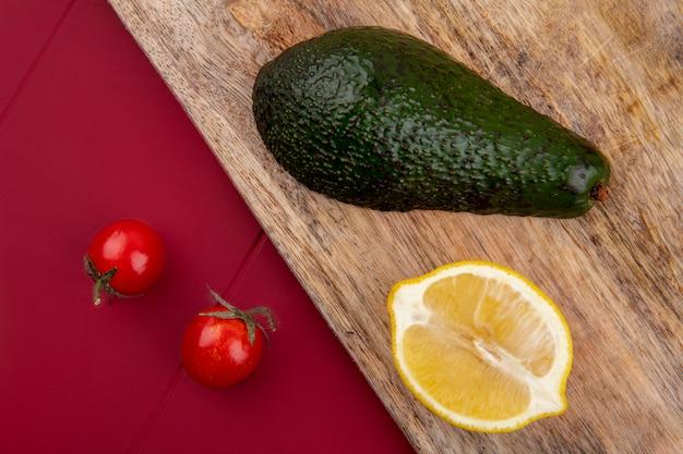 Widok Z Góry Na Zielone I świeże Awokado Na Drewnianej Desce Kuchennej Z Plasterkiem Cytryny I Pomidorkami Cherry Na Czerwonej Powierzchni Darmowe Zdjęcia