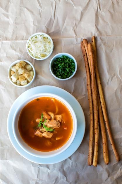 Widok z góry na zupę z owoców morza podawaną z paluszkami i kostkami, tartym serem, ziołami Darmowe Zdjęcia