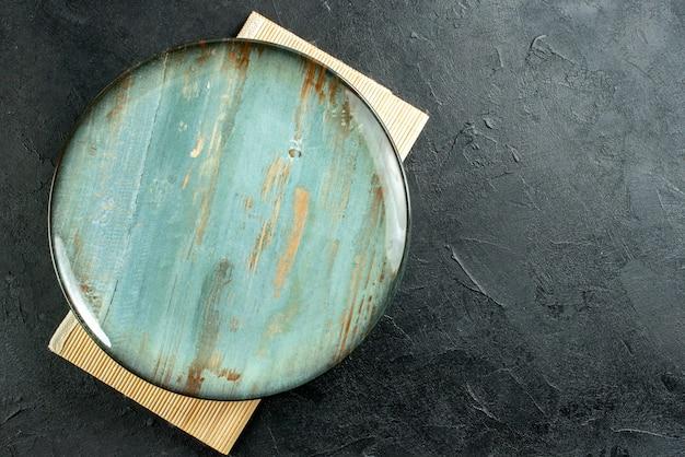 Widok Z Góry Niebiesko-zielony Okrągły Talerz Beżowy Talerz Na Czarnym Stole Z Wolną Przestrzenią Darmowe Zdjęcia