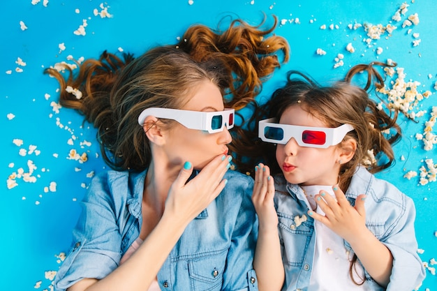 Widok Z Góry Niesamowita Radosna Dziewczyna R. Z Matką W Popcorn Na Niebieskiej Podłodze. Noszenie Okularów 3d, Patrzenie Na Siebie, Wspólna Zabawa, Wyrażanie Prawdziwych Szczęśliwych Rodzinnych Emocji Darmowe Zdjęcia