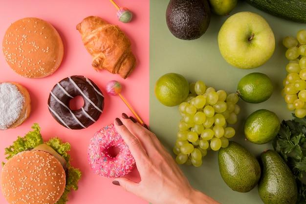 Widok Z Góry Niezdrowe Jedzenie Kontra Zdrowe Jedzenie Z Ręki Trzymającej Pączek Darmowe Zdjęcia
