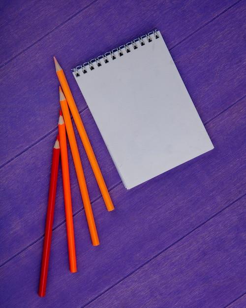 Widok Z Góry Notesu I Kolorowych Ołówków Na Fioletowym Tle Z Miejsca Na Kopię Darmowe Zdjęcia