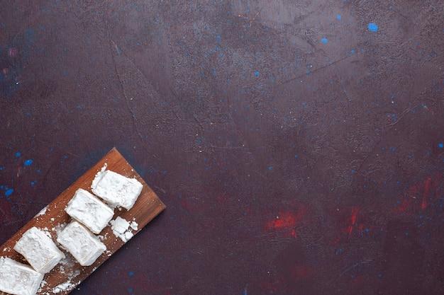 Widok Z Góry Nugatu Cukierków W Proszku Na Ciemnej Powierzchni Darmowe Zdjęcia