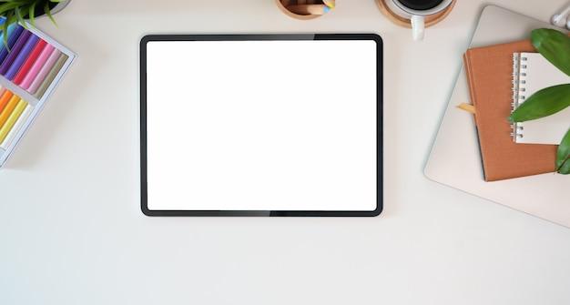 Widok z góry obszaru roboczego biurka na obecny produkt reklamowy na ekranie tabletu Premium Zdjęcia