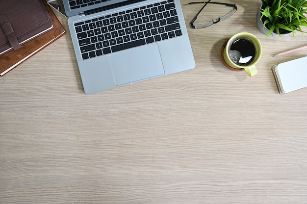 Widok z góry obszaru roboczego z laptopa, kawy, szklanek, książek i dekoracji roślin na stół z drewna biura. Premium Zdjęcia