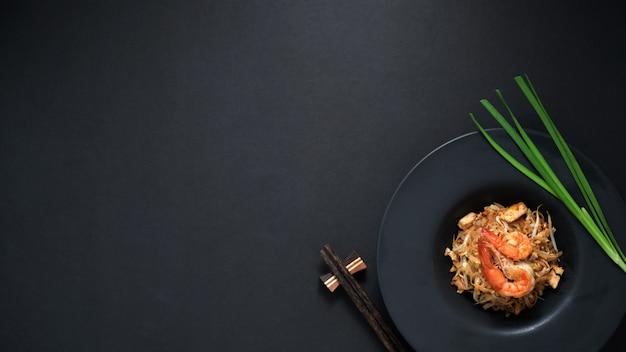 Widok Z Góry Pad Thai, Wymieszaj Muchę Tajskiego Kluski Z Krewetkami I Jajkiem W Czarnym Talerzu Ceramicznym Na Czarnym Stole Premium Zdjęcia