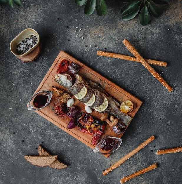 Widok Z Góry Pieczonej Ryby Z Warzywami Cytrynowymi I Sosem Z Granatu Narsharab Na Drewnianej Desce Na Ciemnej ścianie Darmowe Zdjęcia