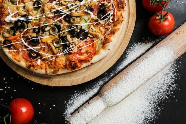 Widok Z Góry Pizza Na Stojaku Z Pomidorami, Oliwkami, Wałkiem Do Ciasta I Mąką Na Czarnym Stole Darmowe Zdjęcia