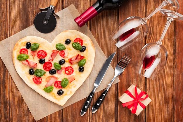 Widok z góry pizza w kształcie serca z winem i prezentem Darmowe Zdjęcia