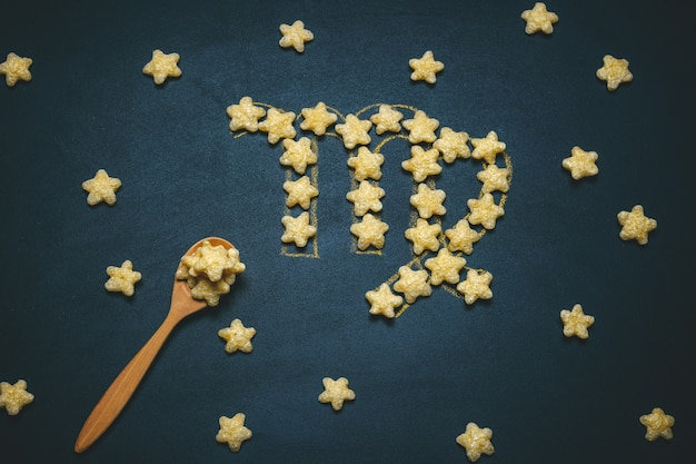 Widok Z Góry Płasko Leżący Znak Virgo Horoskop Wykonany Z Chrupiących Gwiazd Kukurydzy Na Czarnym Premium Zdjęcia