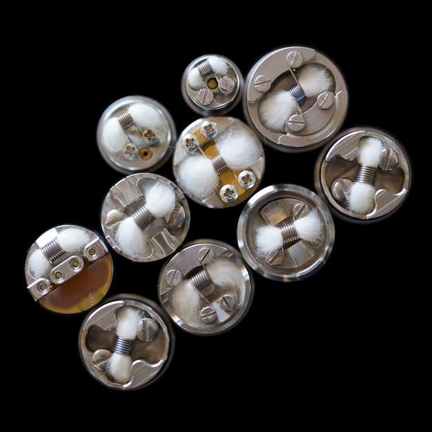 Widok z góry pojedynczej mikro cewki z bawełną w kapilarnych rozpylaczach z możliwością odbudowy na białym tle na czarny ba Premium Zdjęcia