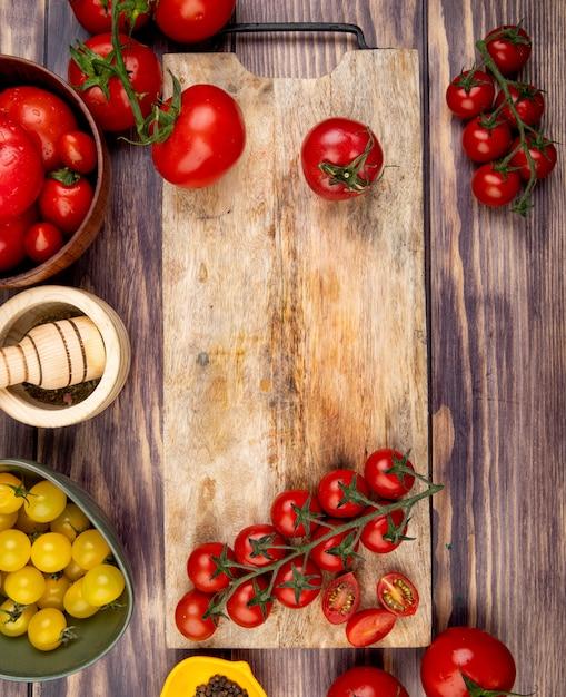 Widok Z Góry Pokrojonych I Całych Pomidorów Na Desce Do Krojenia Z Innymi Kruszarkami Czosnku Pieprz Czarny Na Powierzchni Drewnianych Darmowe Zdjęcia
