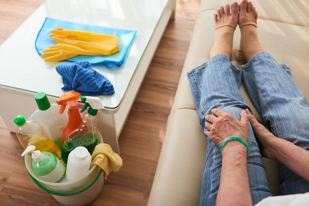Widok z góry przeklętej kobiety siedzącej na kanapie, dotykającej bolesnego kolana wyczerpanego rutyną sprzątania Darmowe Zdjęcia