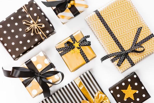 Widok z góry pudełek prezentowych w różnych czarnych, białych i złotych wzorach. leżał płasko. koncepcja świąt bożego narodzenia, nowego roku, obchodów urodzin. Premium Zdjęcia