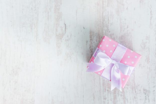 Widok z góry pudełka prezentowego owiniętego różowym kropkowanym papierem i wiązanej satynowej kokardki nad białym drewnem. Premium Zdjęcia