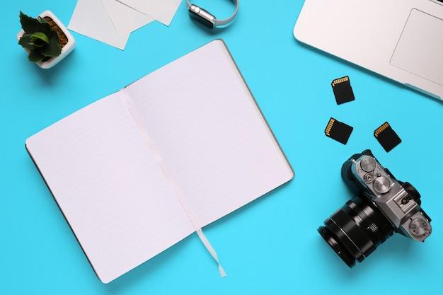 Widok z góry pulpitu fotografa składającego się z aparatu, laptopa, notebooka i karty pamięci na niebieskim tle biurka - kopia przestrzeń. Premium Zdjęcia