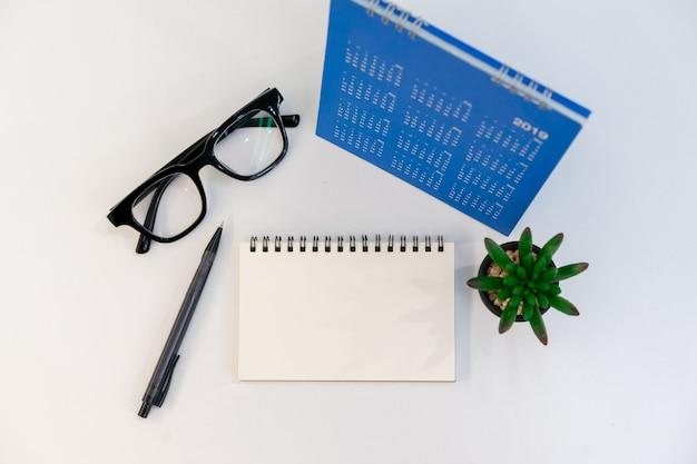 Widok z góry pustego notatnika, ołówek, okulary, kalendarz i mały zakład na stole Premium Zdjęcia