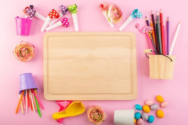 Widok Z Góry Pusty Drewniany Stół Z Ołówkami Cukierki Kwiaty Na Różowym Kolorze Dekoracji Uroczystości Stołu Darmowe Zdjęcia