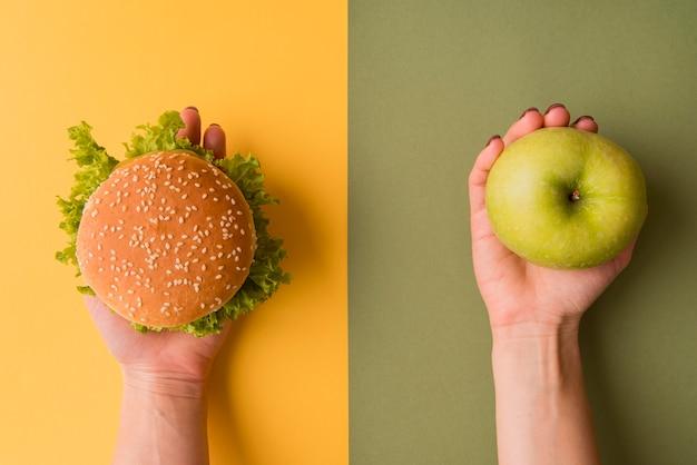 Widok Z Góry Ręce Trzymając Burger I Jabłko Premium Zdjęcia
