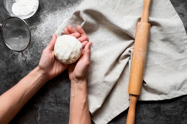 Widok Z Góry Ręce Trzymające Ciasto W Pobliżu Wałka Do Ciasta Premium Zdjęcia