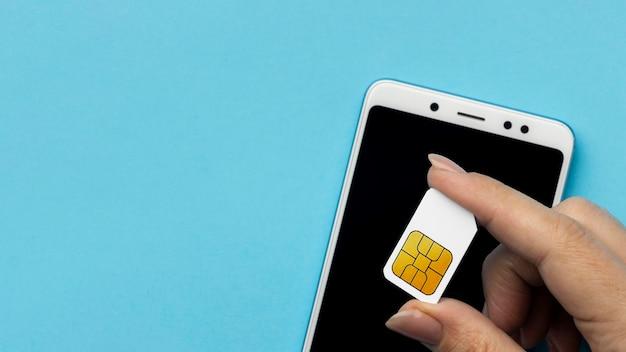 Widok Z Góry Ręki Trzymającej Kartę Sim Ze Smartfonem I Miejscem Na Kopię Darmowe Zdjęcia