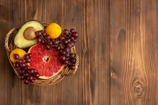 Widok Z Góry Różne Owoce W Koszu Na Brązowym Drewnianym Biurku Darmowe Zdjęcia