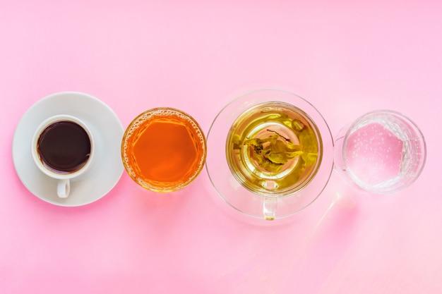 Widok Z Góry Różnych Napojów - Picie Kawy, Wody Gazowanej, Soku Jabłkowego I Zielonej Herbaty Na Różowym Tle. Pojęcie Zdrowego życia I Diety Premium Zdjęcia