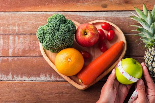 Widok Z Góry Różnych świeżych Organicznych Owoców I Warzyw W Talerz Serca I Ręce Kobiety Premium Zdjęcia