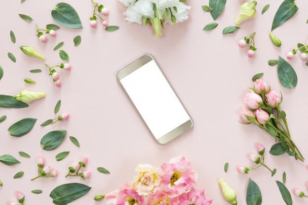 Widok Z Góry Różowe Biurko Z Nowoczesnym Złotym Telefonem Komórkowym I Ramką Z Kwiatem Premium Zdjęcia